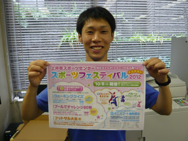 スタッフ矢谷くんが今年のチラシを持っています!